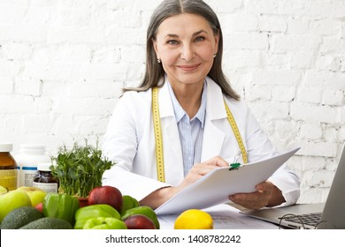 Horizontal shot of beautiful positive elderly female nutritionist having consultation with client at her office, holding papers, prescribing nutritional supplements and vitamins, smiling at camera
