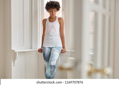 Horizontal shot of beautiful thoughtful dark skinned girl dressed in casual white t shirt and leggings, has sporty fit figure, feels lonely, stands near window, has rest after workout in gym.