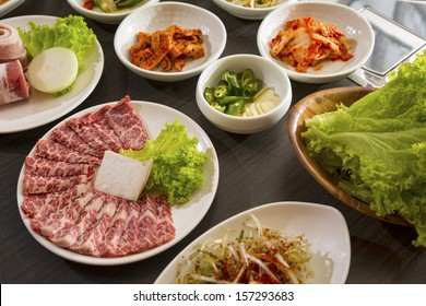 A horizontal shot of beef with korean side dishes.