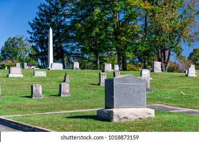 Horizontal shot of a blank tombstone in a cemetary.  Green trees and blue sky behind it.