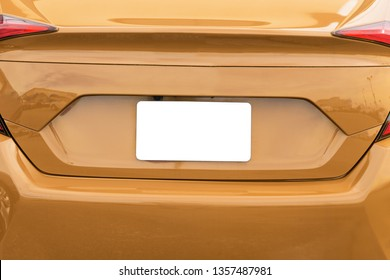 Horizontal shot of a blank white license plate on a gold car with copy space.