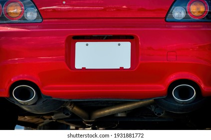 Horizontal shot of a blank white license plate on a red car bumper.  This is a revised image.