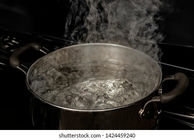 Horizontal shot of boiling water in a Dutch oven on a stovetop.