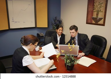 A horizontal shot a businessman and two businesswomen looking at papers and laptops.