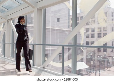 Horizontal shot of a businesswoman, talking on a cellphone, walking through a skybridge