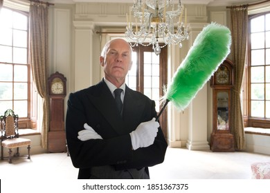 Horizontal shot of a butler standing with arms crossed and holding a duster in his hands while cleaning and posing confidently