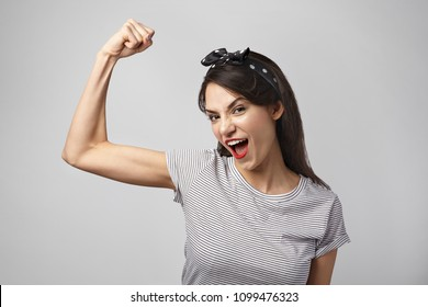 Horizontal shot of casually dressed young lady wearing bright make up and headscarf shouting fiercely and tensing bicep, showing strength and power. Pretty girl with fit body demonstrating muscles