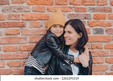 Horizontal shot of charming friendly little child and her mother embrace each other, dressed in black leather jackets, have appealing look and pleasant smile pose over brick wall. Relationship concept