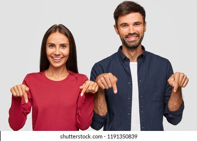 Horizontal shot of cheerful Caucasian young adult woman and man point with index fingers down, satisfied to advertise new object, have pleasant smiles on faces, isolated over white background