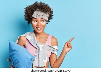 Horizontal shot of cheerful ethnic girl in nightclothes smiles positively indicates at upper right corner holds pillow demonstrates product for rest isolated over blue background. People and sleeping