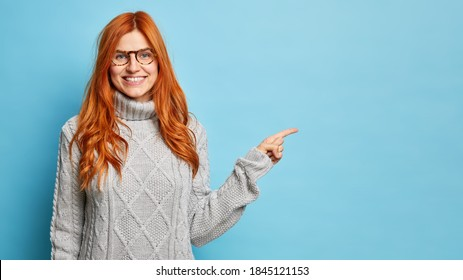 Horizontal shot of cheerful redhead European woman in spectacles smiles broadly and points away on copy space gives direction to best shop wears warm winter sweater isolated over blue background