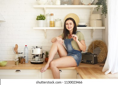 Horizontal shot of cheerful young brunette plus size woman in denim jumpsuit sitting on wooden kitchen counter and having unhealthy chocolate doughnut or bagel. Sugar, gluttony and obesity