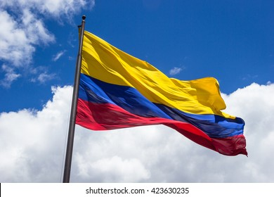 Horizontal shot of the colombian flag being move by the wind over sky and clouds on a sunny day.