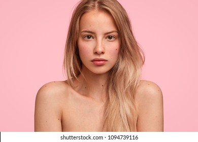 Horizontal shot of confident beautiful woman has healthy skin after applying mask or body cream, takes care of her appearance, stands half naked indoor, relaxed after hard day, going have shower