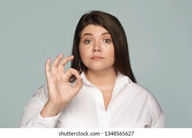 Horizontal shot of confident serious overweight chubby female manager dressed in white formal shirt connecting fore finger and thumb, making ok gesture, showing that everything is under control