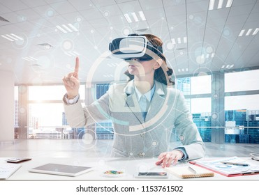Horizontal shot of confident young business woman in suit using virtual reality headset and safety interface while sitting inside office building.