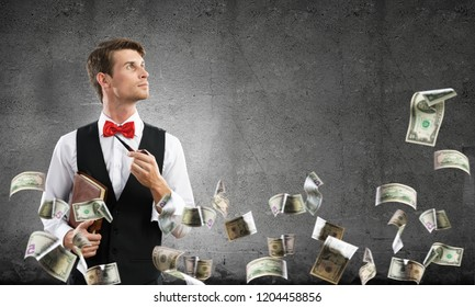Horizontal shot of confident and young businessman in smart-casual wear smoking pipe while standing among flying dollars and against gray dark wall on background.