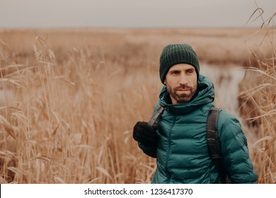 Horizontal shot of contemplative good looking man has stubble, wears hat, jacket and gloves, stands near wheat field background with free space on right side. People, leisure and walk concept