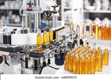 Horizontal shot of cosmetics or pharmacy plant with automated equipment. Transparent plastic bottles filled with yellow substance standing on desk and conveyor line, ready for transportation