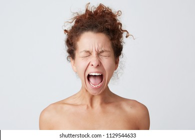 Horizontal shot of crazy hysterical young woman with curly hair and soft healthy skin close eyes and sceaming isolated over white background Looks stressed and feels angry