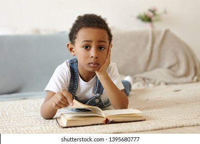 Horizontal shot of cute charming dark skinned African boy lying on floor in his room leaning on elbow, looking at camera with serious expression, enjoying favorite hobby, reading his first book