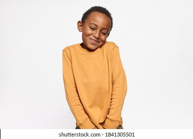 Horizontal shot of cute handsome dark skinned little boy shrugging shoulders feeling embarrassed with uncomfortable question, looking down with shy timid smile. Human emotions and body language