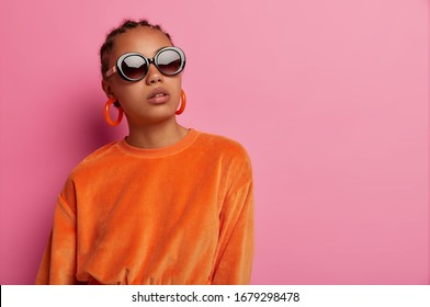 Horizontal shot of dark skinned female model wears stylish velvet orange sweater and earrings, big sunglasses, poses serious, buys clothes of last trends, poses against pink background, empty space