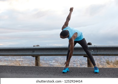 Horizontal shot of dark skinned man leans to feet, does stretching exercises, has muscular body shape, stands on asphalt over light blue sky with copy space for your advertising content, text
