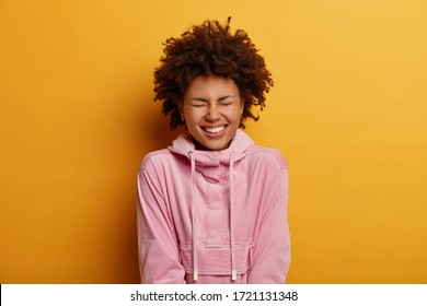 Horizontal shot of dark skinned young woman laughs at something funny, giggles over hilarious joke, rejoices positive event, wear rosy hoodie, models indoor. People, happiness, lifestyle concept