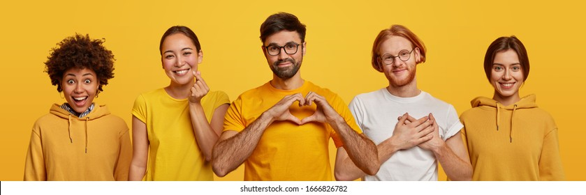 Horizontal shot of different diverse people make heart gesture, being thankful, Asian woman makes korean like sign, wear yellow clothes, stand in one row against bright background. Body language