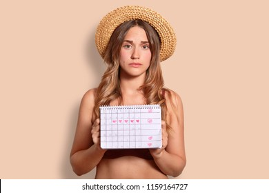 Horizontal shot of displeased young European female tourist in summer straw hat holds period calendar, has unhappy look as going to have menstuation during rest, isolated over beige studio wall