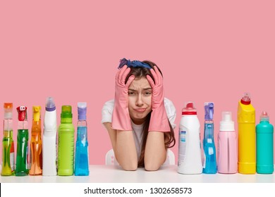 Horizontal shot of dissatisfied young housemaid keeps hands on head, cries desperately, being tired of housework, wears pink rubber gloves, surrounded with cleaning detergent, has sad expression