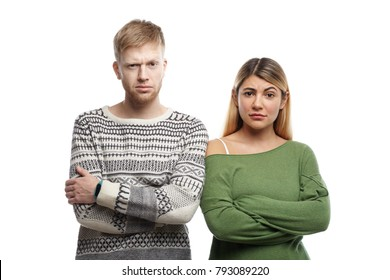Horizontal shot of distrustful young couple crossing arms in studio and staring at camera, having doubtful skeptical looks. Human facial expressions, emotions, feelings, attitude and body language