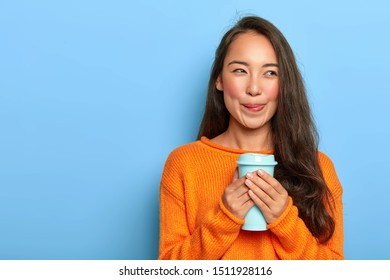 Horizontal shot of dreamy Asian girl licks lips, enjoys taste of aromatic coffee, has long dark hair, wears orange jumper, looks away, poses against blue background. People, drinking, spare time