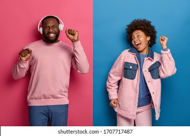 Horizontal shot of ethnic boyfriend and girlfriend dance carefree, enjoy awesome headphones bits, smile happily, raise hands, have fun together at disco party, pose against two colored background