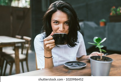 Horizontal shot of European woman dressed in white t-shirt drinking coffee or tea thoughtfully out of big cup, looking front with happy expression, enjoy the break. People and lifestyle concept.