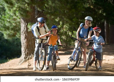 Horizontal shot of a family of four mountain biking along a woodland trail with father adjusting strap of daughter's cycling helmet.