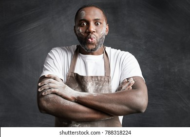 Horizontal shot of funny black male chef of famous restaurant stands crossed hands, rounds lips, has dirty face and clothes with flour, isolated over black chalk background. Handsome cook indoor