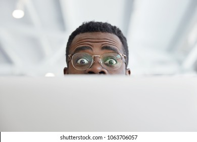 Horizontal shot of funny dark skinned male in big round glasses, looks from laptop computer, has funny expression, shocked to have deadline and much work. People, facial expressions, technology