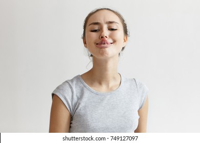 Horizontal shot of funny humorous playful young European woman in grey t-shirt sticking out her tongue, trying to touch nose with its tip. People, youth, leisure, joy, fun and entertainment concept.