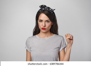 Horizontal shot of gorgeous beautiful girl wearing red lipstick, headband and sailor shirt pouting lips, having serious confident look, showing clenched fist. Feminism, equality and women's liberation