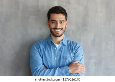Horizontal shot of handsome Caucasian guy pictured isolated on grey background standing with arms crossed in casual clothes, looking confident and optimistic, smiling friendly and happily while posing