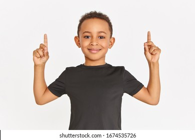 Horizontal shot of handsome sporty Afro American boy in stylish black t-shirt posing isolated with fore fingers raised pointing fore fingers upwards, showing copy space for your information