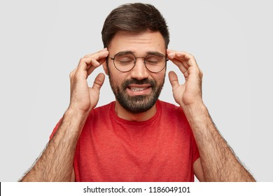 Horizontal shot of handsome unshaven man with dark hair, keeps hands on temples, closes eyes, concentrates or remembers something, dressed in red casual t shirt, isolated over white background