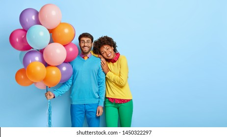 Horizontal shot of happy birthday man holds colorful balloons, Afro girl leans on his shoulder, wait for guests together, have broad smiles, isolated on blue wall with blank space. People and holiday