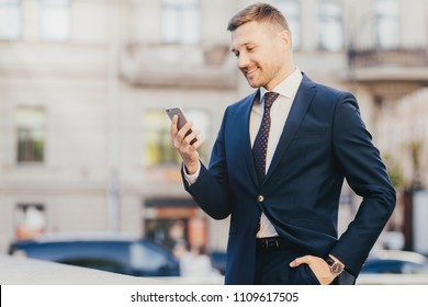 Horizontal shot of happy businessman keeps hand in pocket, wears formal suit and wristwatch, recieves notification on smart phone, finds out about high financial balance. Cheerful trader outdoor