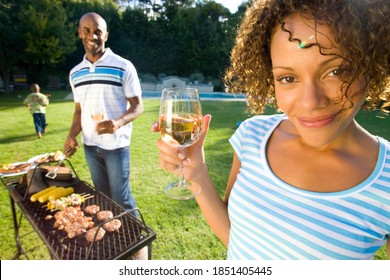 Horizontal shot of a happy couple having barbeque outdoors with the woman holding a glass of wine in the foreground and her husband on barbeque in the background.