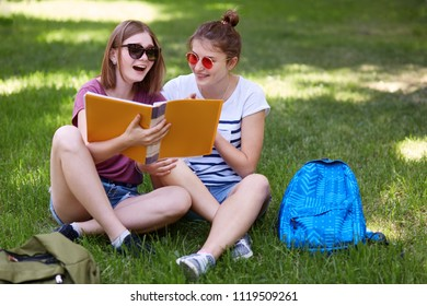 Horizontal shot of happy female studens feels relaxed while sit crossed legs on green grass, enjoy spring weather, have positive expressions, rests after classes. People, rest, leisure concept