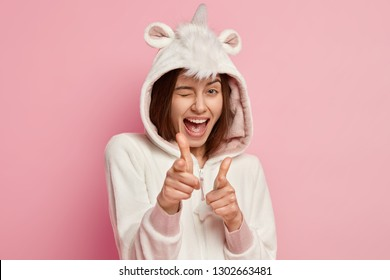 Horizontal shot of happy girl wears funny kigurumi costume, blinks with eyes and makes finger gun gesture, has ears and horn, chooses you, isolated over pink background. Sleepwear fashion concept
