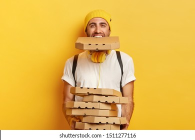 Horizontal shot of happy male courier overloaded with carton pizza boxes, holds stack of cardboard containers and one in mouth, dressed in casual wear, isolated over yellow wall. Fast food concept